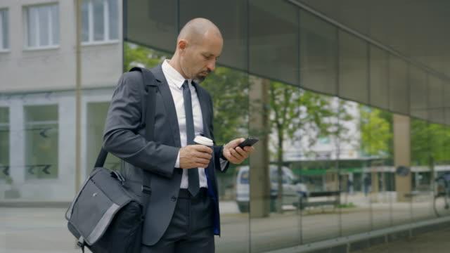 stockvideo's en b-roll-footage met slo mo zakenman die de tijd controleert terwijl het gebruiken van zijn smartphone tijdens koffieonderbreking - alleen mid volwassen mannen