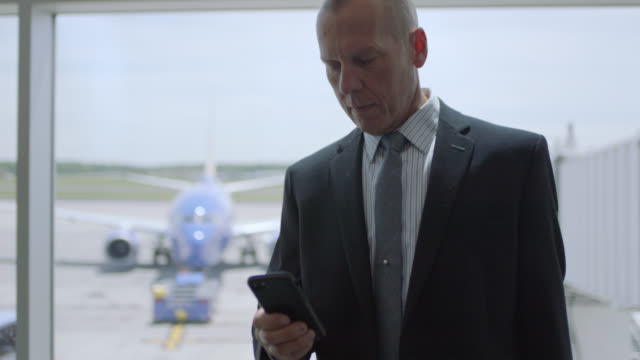 slo mo. businessman checks smartphone while standing near gate window in airport terminal. - geschäftsreise stock-videos und b-roll-filmmaterial
