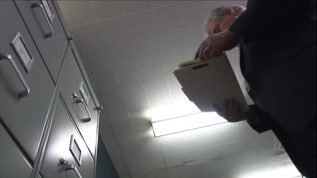 a businessman closes a file cabinet and takes a file folder as he exits his office. - storage compartment stock videos & royalty-free footage
