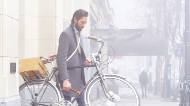MS businessman commuting from work carrying bike down steps of office building and riding away