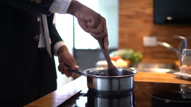 vídeos de stock e filmes b-roll de businessman cooking at home - domestic kitchen