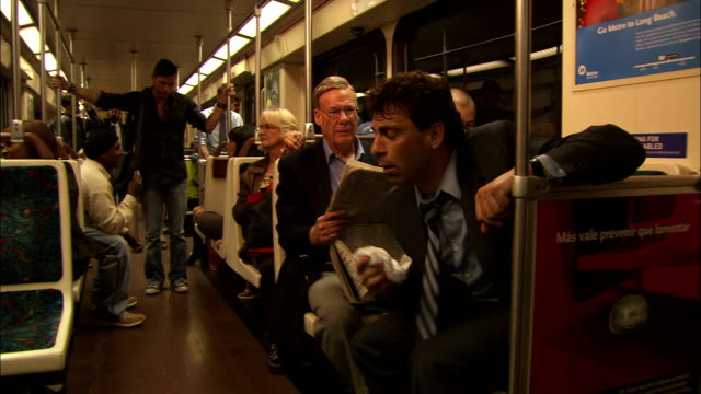 vídeos y material grabado en eventos de stock de a businessman coughs and sneezes on a crowded subway train. - enfermedad contagiosa