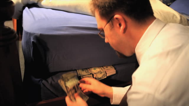CU Businessman counting money and taking some from under mattress, Appleton, Wisconsin, USA