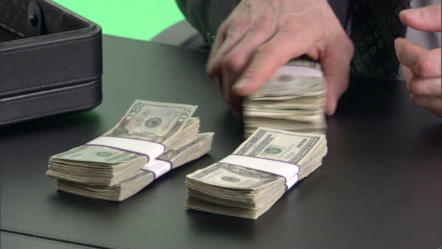 ecu, businessman counting money at desk in studio, close-up of hands - aktentasche stock-videos und b-roll-filmmaterial