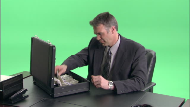 vidéos et rushes de ms, businessman counting money at desk in studio - billet de banque