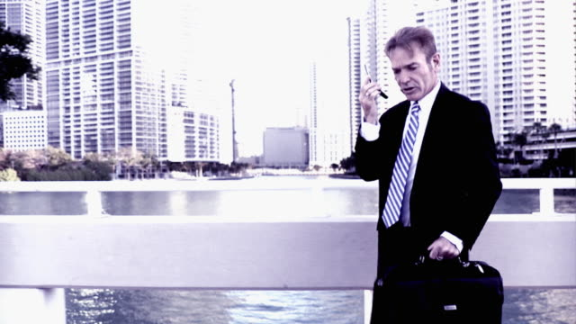 vidéos et rushes de slo mo cross process businessman crossing bridge and talking on mobile phone, south beach, florida - procédé croisé