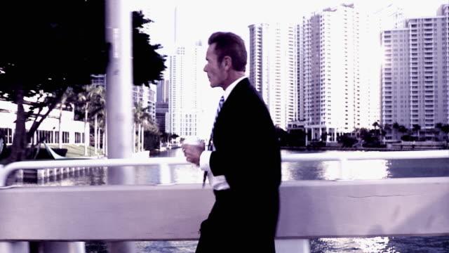 vidéos et rushes de slo mo cross process businessman crossing bridge, drinking from disposable cup, south beach, florida - procédé croisé