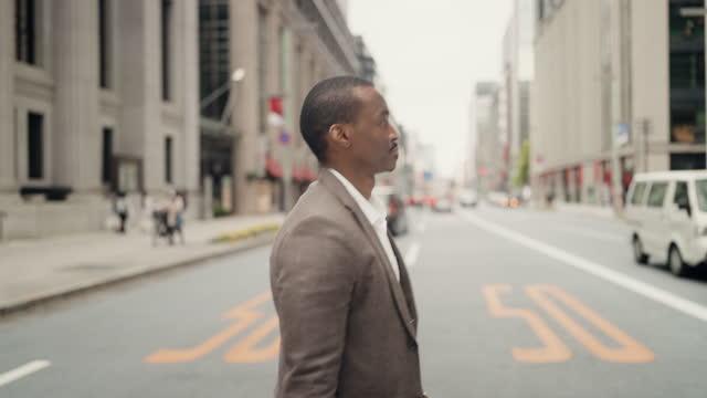 vídeos y material grabado en eventos de stock de empresario cruzando calle en distrito financiero de la ciudad - crossing
