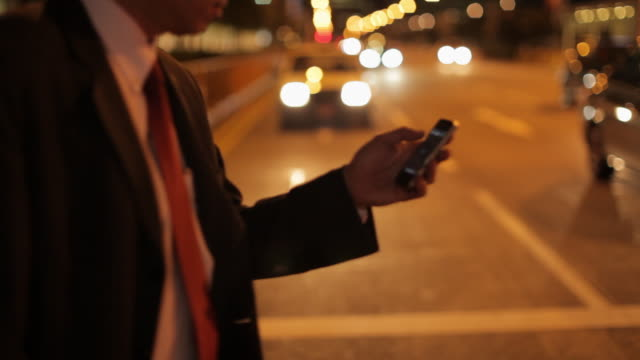 mh ts businessman crossing street while texting on phone at night / singapore - überqueren stock-videos und b-roll-filmmaterial