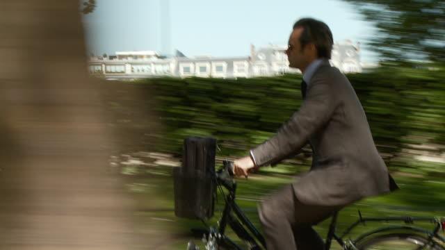 vidéos et rushes de ms ts td tu side pov businessman cycling along tree-lined path, esplanade habib bourguiba, paris, france - vue latérale
