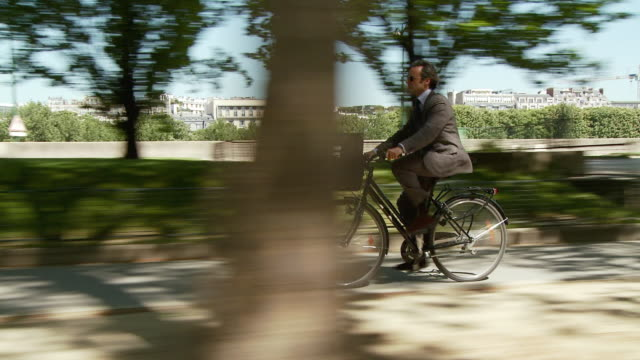 WS TS SIDE POV Businessman cycling along tree-lined path, Esplanade Habib Bourguiba, Paris, France