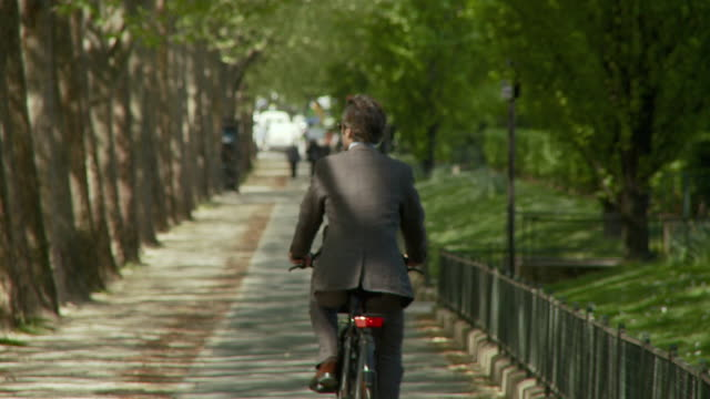 WS Businessman cycling away from camera along tree-lined path, Esplanade Habib Bourguiba, Paris, France