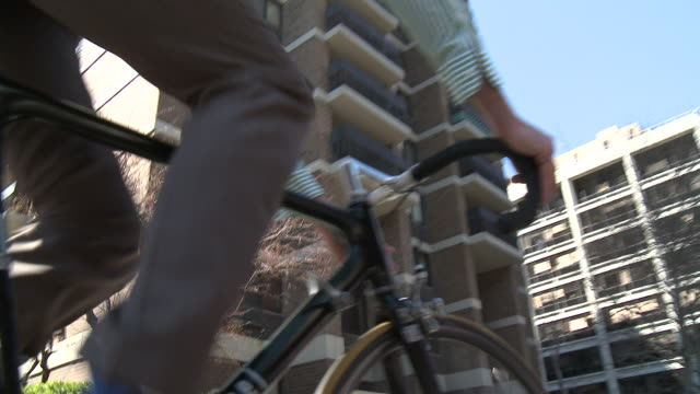 cu ts la businessman cycling down street, new york city, new york, usa - pendler stock-videos und b-roll-filmmaterial