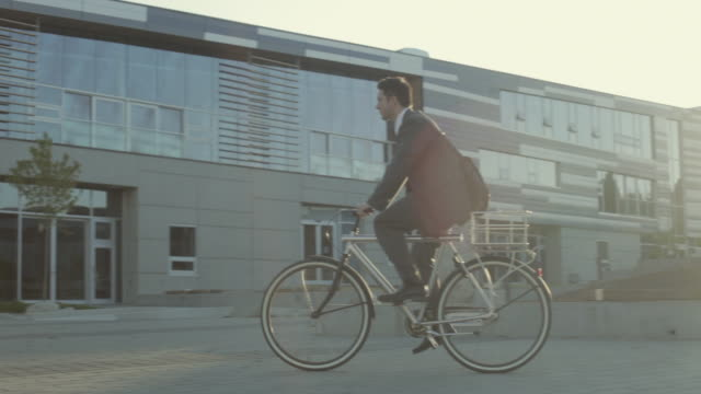 vidéos et rushes de ws pan businessman cycling towards office building in morning / vancouver, british columbia, canada - 30 34 ans