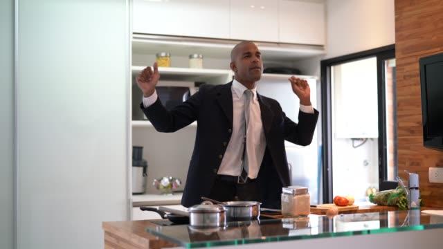 vídeos de stock e filmes b-roll de businessman dancing and cooking at home - domestic kitchen