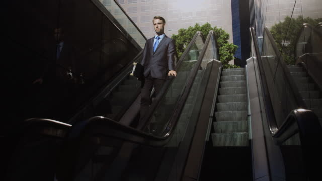 vídeos de stock e filmes b-roll de businessman descending escalator into shadow - com sombra