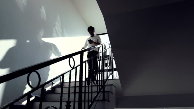 businessman descending stairs and using mobile phone in office - scale video stock e b–roll