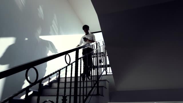 vídeos de stock e filmes b-roll de businessman descending stairs and using mobile phone in office - degraus e escadas