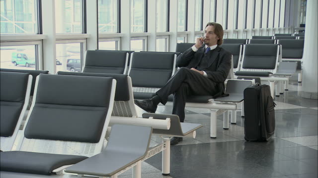 WS Businessman dialing mobile phone and sitting in airport lounge / Munich, Germany