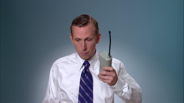 vídeos de stock e filmes b-roll de ms businessman dialing on large, early mobile phone and having conversation/ new york city - camisa e gravata