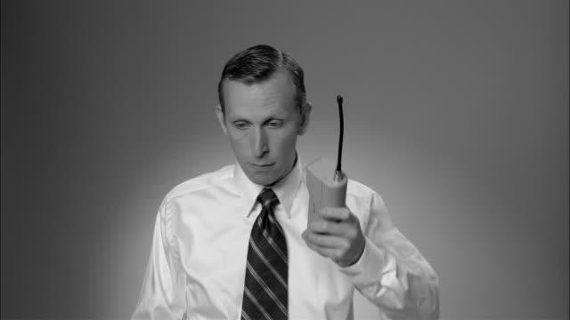 b/w ms businessman dialing on large  early mobile phone and having conversation/ new york city - sladdlös telefon bildbanksvideor och videomaterial från bakom kulisserna