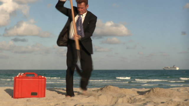 ws businessman digging and burring suitcase in sand / south beach, florida, usa - buried stock videos & royalty-free footage