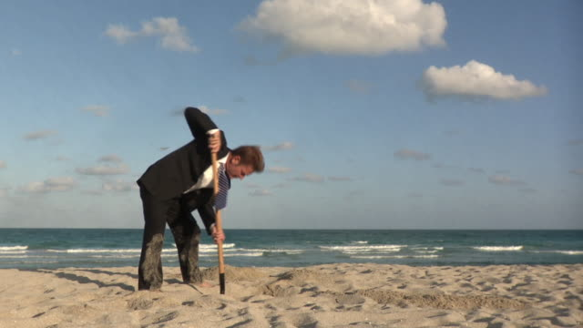 ws businessman digging hole in sand with shovel on beach / south beach, florida, usa - digging stock videos & royalty-free footage