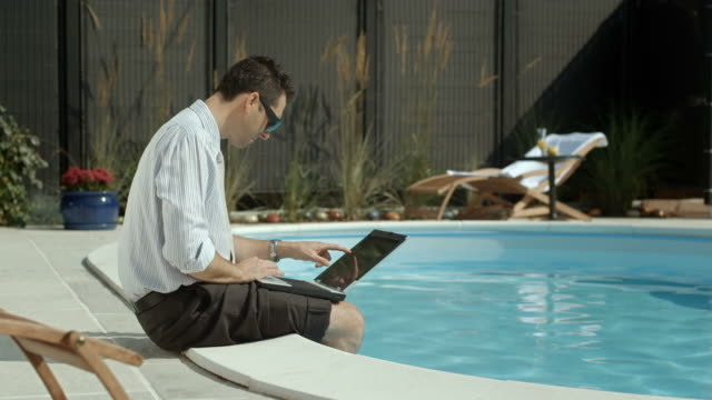 hd: businessman dipping his feet in the pool - outdoor chair stock videos & royalty-free footage