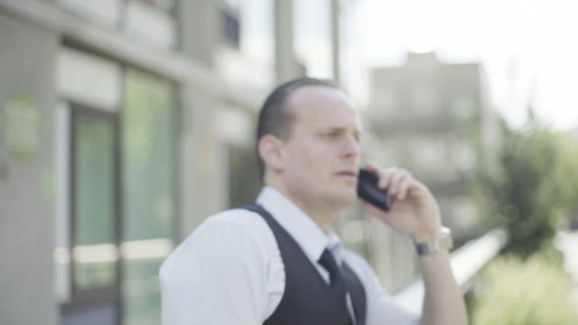 businessman discussing business on cell phone - hochgekrempelte ärmel stock-videos und b-roll-filmmaterial