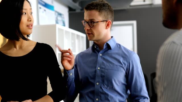 vídeos de stock e filmes b-roll de businessman discussing with colleagues at office - grupo pequeno de pessoas