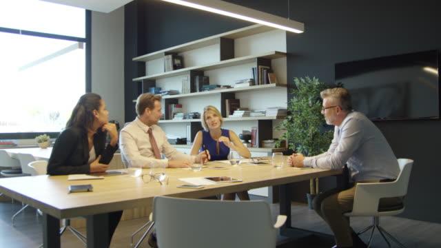 vidéos et rushes de homme d'affaires, discutant avec des collègues à table - chaise de bureau