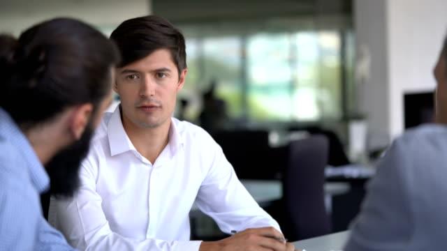vídeos y material grabado en eventos de stock de businessman discussing with coworkers at table - compromiso de los empleados