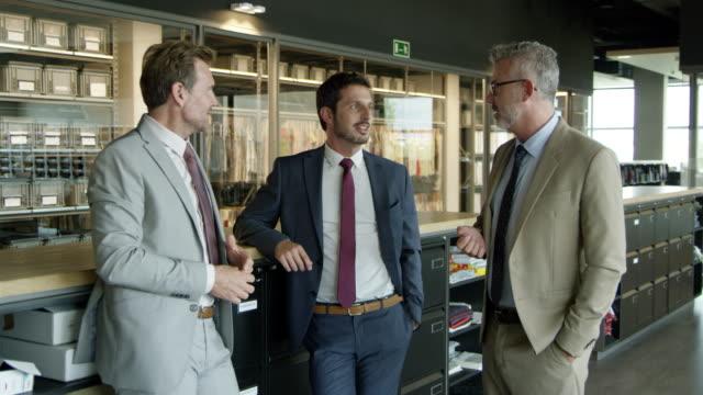 vídeos de stock e filmes b-roll de businessman discussing with coworkers in office - três pessoas