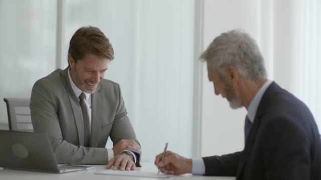 vidéos et rushes de homme d'affaires discutant avec le associé dans le bureau - accord concepts