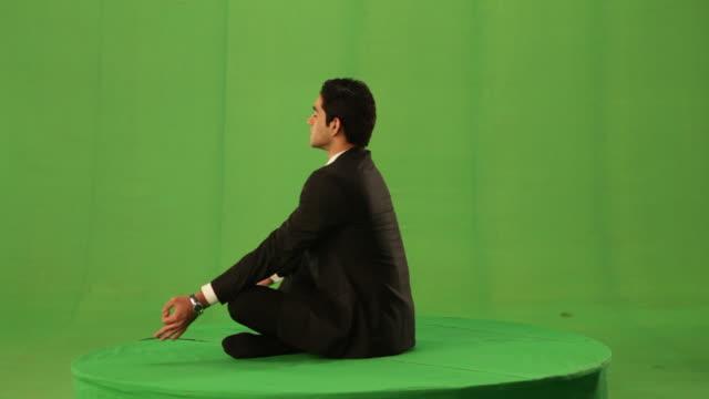 Businessman doing padmasana