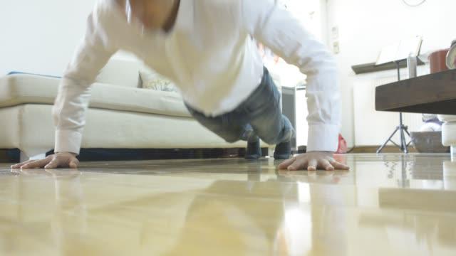 vídeos y material grabado en eventos de stock de businessman doing push-up at home and then dog come to play with him - entrenamiento sin material
