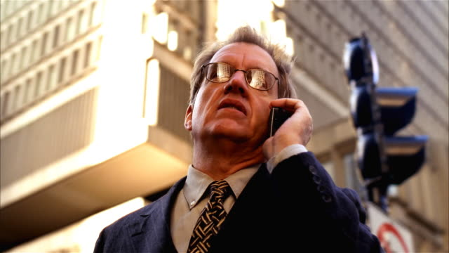 businessman downtown on cellular phone - formato video mpeg video stock e b–roll