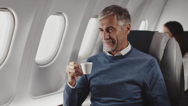 vídeos de stock, filmes e b-roll de empresário bebendo café em avião particular - só um homem maduro