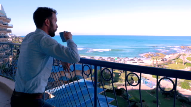 Businessman drinking coffee on balcony - Stock Video