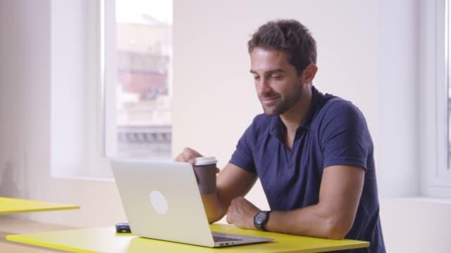 affärsmannen dricker kaffe medan du använder laptop - engångsmugg bildbanksvideor och videomaterial från bakom kulisserna