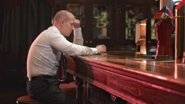 HD DOLLY: Businessman Drinking In Despair