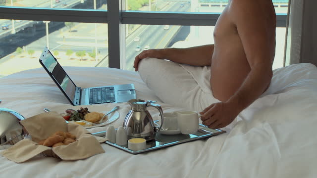 ms pan tu businessman drinking tea and using laptop in hotel room / cape town, cape town, south africa - wrapped in a towel stock videos and b-roll footage