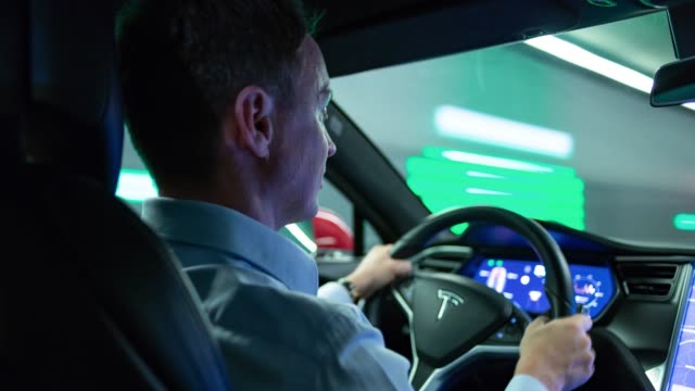 businessman drives with electric powered tesla model s car on city highway and through tunnels while night. - 自動車産業点の映像素材/bロール