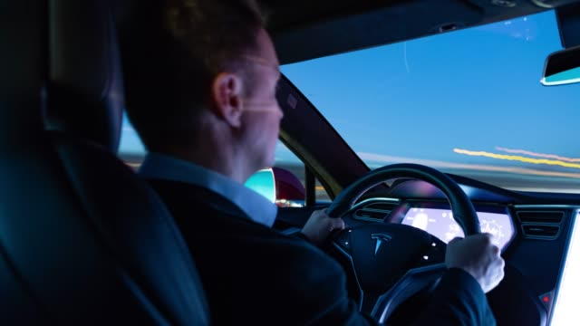 vídeos de stock, filmes e b-roll de businessman drives with electric powered tesla model s on highway while dawn. - long exposure