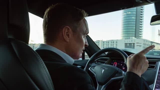 businessman drives with electric powered tesla model s through the city of munich. - made in the usa kort fras bildbanksvideor och videomaterial från bakom kulisserna