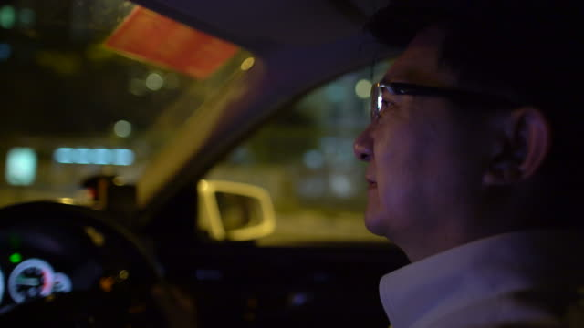 cu businessman driving a  car in city at night - only mature men stock videos & royalty-free footage