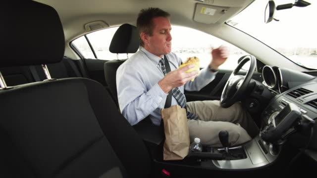 vídeos de stock, filmes e b-roll de ms businessman driving car and eating lunch / orem, utah, usa - interior de carro
