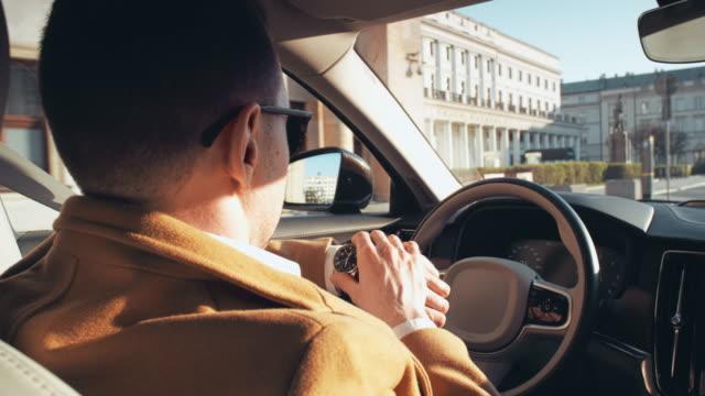 businessman driving through city center. autonomos car interior. passing - driverless car stock videos & royalty-free footage