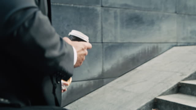 stockvideo's en b-roll-footage met slo mo zakenman die een hamburger eet en koffie drinkt terwijl het lopen op treden - mid volwassen mannen