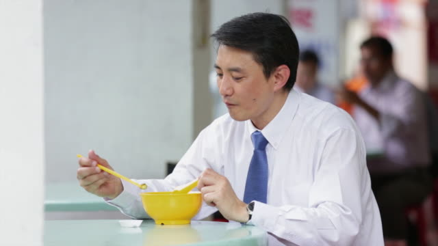 WS Businessman eating bowl of noodles at food court